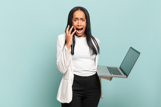 Young black woman looking desperate and frustrated, stressed, unhappy and annoyed, shouting and screaming. laptop concept
