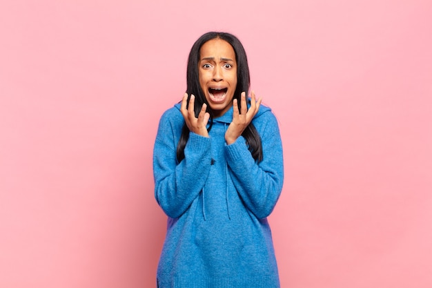 Young black woman looking desperate and frustrated, stressed, unhappy and annoyed, shouting and screaming