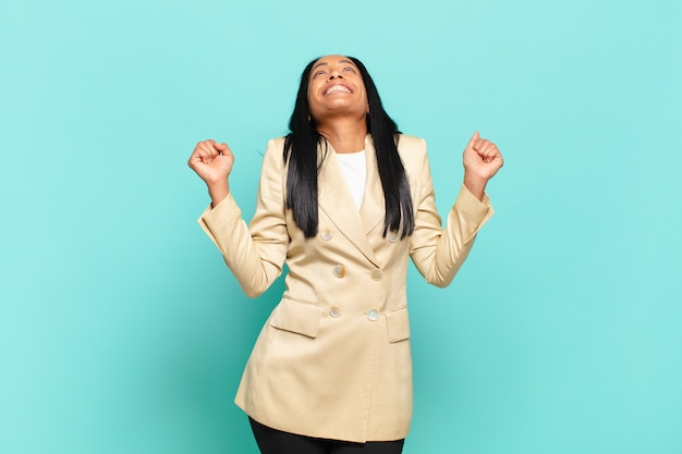 Молодая темнокожая женщина выглядит очень счастливой и удивленной, празднует успех, кричит и прыгает