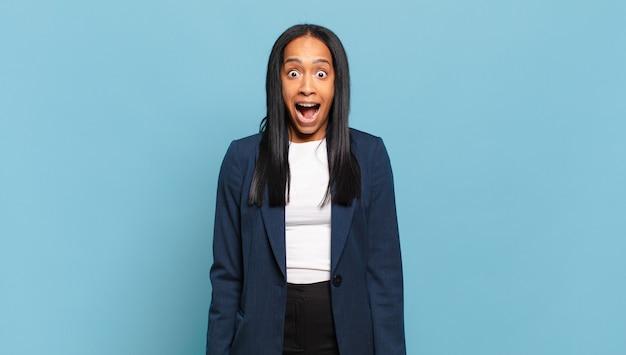 Молодая темнокожая женщина выглядит счастливой и приятно удивленной, взволнованной, с очарованным и шокированным выражением лица. бизнес-концепция
