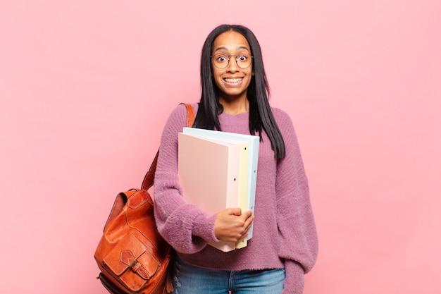 Молодая темнокожая женщина выглядит счастливой и приятно удивленной, взволнованной, с очарованным и шокированным выражением лица. студенческая концепция