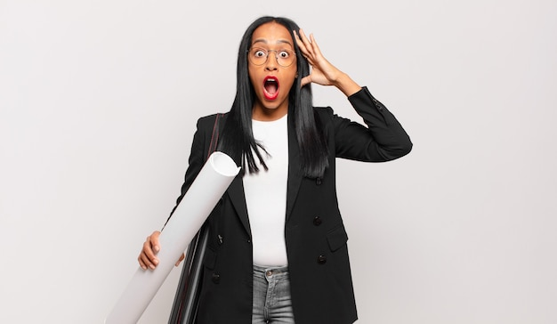 Young black woman looking happy, astonished and surprised, smiling and realizing amazing and incredible good news. architect concept