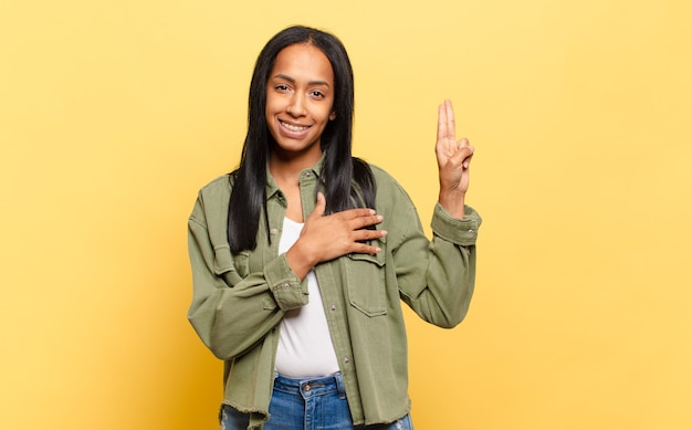 幸せに見え、自信を持って信頼できる若い黒人女性、笑顔で勝利のサインを示し、前向きな姿勢で