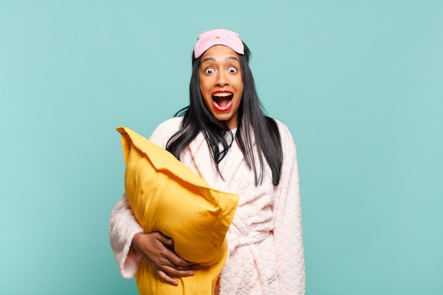 Young black woman looking happy and pleasantly surprised, excited with a fascinated and shocked expression. pajamas concept