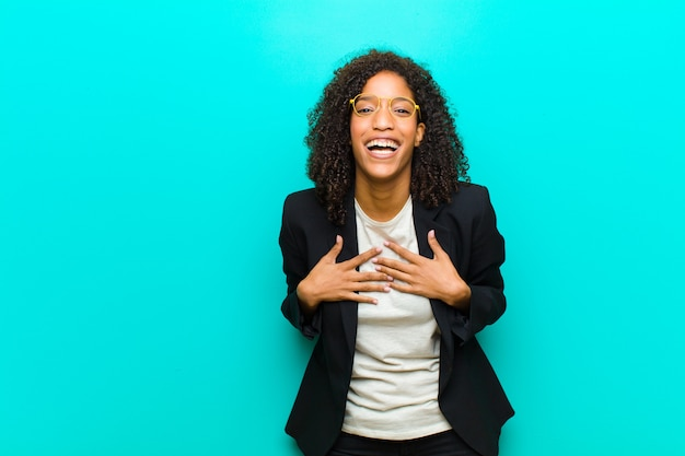 Young black woman looking happy, surprised, proud and excited, pointing to self