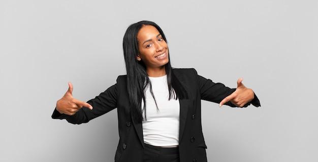誇り高く、傲慢で、幸せで、驚き、満足しているように見え、自己を指して、勝者のように感じている若い黒人女性。ビジネスコンセプト
