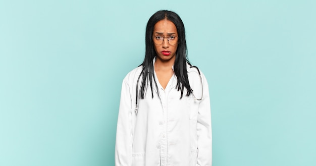 Young black woman looking puzzled and confused, biting lip with a nervous gesture, not knowing the answer to the problem. physician concept