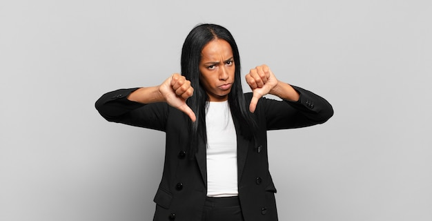 Young black woman looking sad, disappointed or angry, showing thumbs down in disagreement, feeling frustrated. business concept