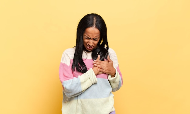 Young black woman looking sad, hurt and heartbroken, holding both hands close to heart, crying and feeling depressed