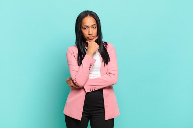 真面目で、混乱し、不確かで思慮深く見え、選択肢や選択肢を疑っている若い黒人女性。ビジネスコンセプト