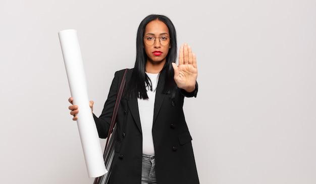 Молодая темнокожая женщина выглядит серьезной, суровой, недовольной и сердитой, показывая открытую ладонь, делая стоп-жест. концепция архитектора