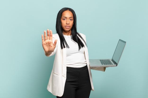 真面目で、厳しく、不機嫌で、怒っているように見える若い黒人女性は、手のひらを開いて停止ジェスチャーを示しています。ノートパソコンのコンセプト