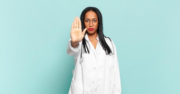 진지하고, 엄하고, 불쾌하고, 화가 난 젊은 흑인 여성이 손바닥을 펴고 정지 제스처를 취하고 있습니다. 의사 개념