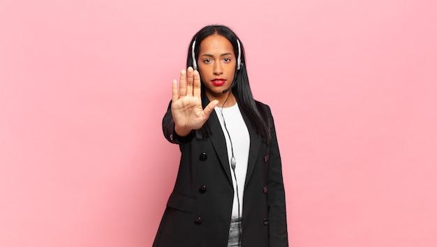 Молодая темнокожая женщина выглядит серьезной, суровой, недовольной и сердитой, показывая открытую ладонь, делая стоп-жест. концепция телемаркетинга