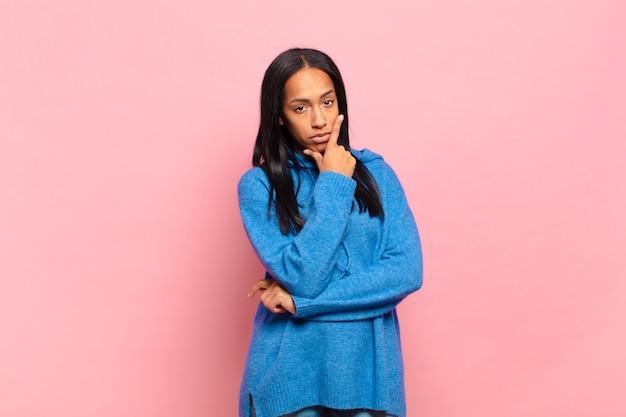 Молодая чернокожая женщина выглядит серьезной, задумчивой и недоверчивой, скрестив одну руку и положив руку на подбородок, варианты взвешивания
