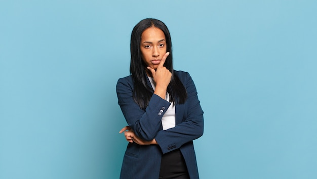 Young black woman looking serious, thoughtful and distrustful, with one arm crossed and hand on chin, weighting options. business concept