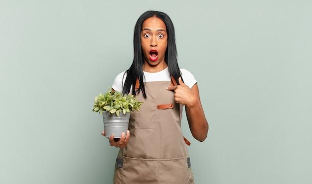 Молодая темнокожая женщина выглядит шокированной и удивленной с широко открытым ртом, указывая на себя. концепция садовника