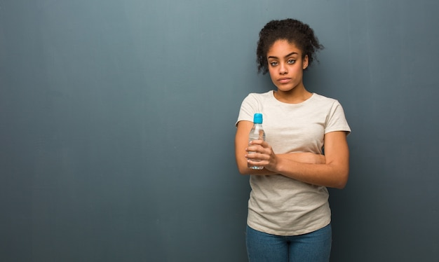 Young black woman looking straight ahead. she is holding a water bottle.