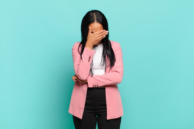 Young black woman looking stressed, ashamed or upset, with a headache, covering face with hand. business concept