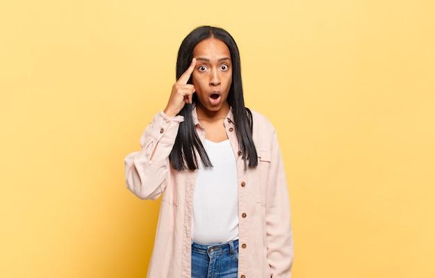 Молодая темнокожая женщина выглядит удивленной, с открытым ртом, шокированной, осознающей новую мысль, идею или концепцию