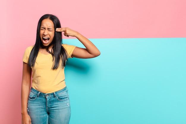 Молодая темнокожая женщина выглядит несчастной и подчеркнутой, жест самоубийства делает знак пистолет рукой, указывая на голову. копировать космическую концепцию