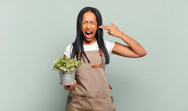 Молодая темнокожая женщина выглядит несчастной и подчеркнутой, жест самоубийства делает знак пистолет рукой, указывая на голову. концепция садовника