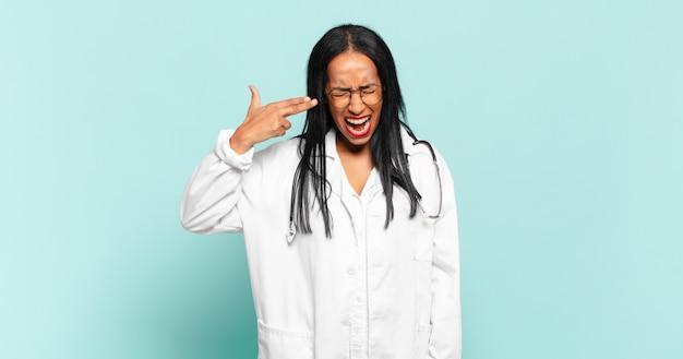 Молодая темнокожая женщина выглядит несчастной и подчеркнутой, жест самоубийства делает знак пистолет рукой, указывая на голову. концепция врача