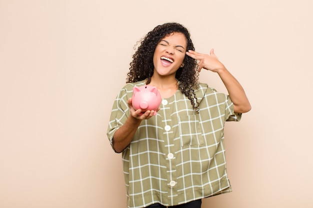 Young black woman looking unhappy and stressed, suicide gesture making gun sign with hand, pointing to head holding a piggy bank