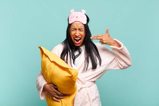 Young black woman looking unhappy and stressed, suicide gesture making gun sign with hand, pointing to head. pajamas concept
