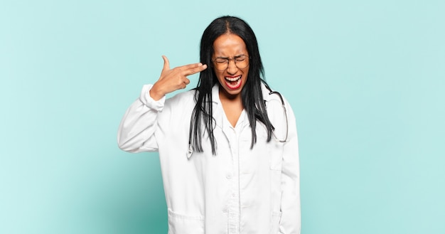 Young black woman looking unhappy and stressed, suicide gesture making gun sign with hand, pointing to head. physician concept