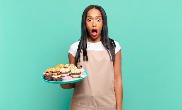 젊은 흑인 여성이 매우 충격을 받거나 놀란 표정으로 입을 벌리고 와우를 쳐다보고 있습니다. 빵집 요리사 개념