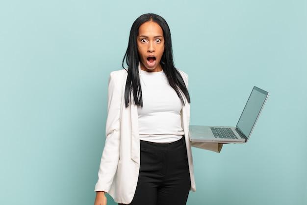 매우 충격을 받거나 놀란 것처럼 보이는 젊은 흑인 여성이 입을 벌리고 와우라고 말합니다. 노트북 개념