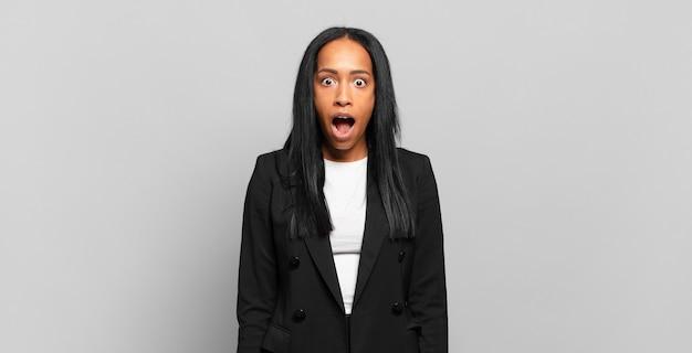 젊은 흑인 여성이 매우 충격을 주거나 놀란 표정으로 입을 벌리고 와우를 쳐다보고 있습니다.