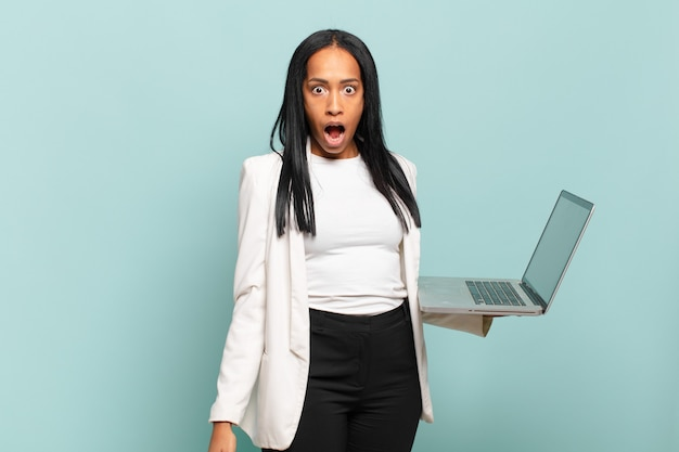 Young black woman looking very shocked or surprised, staring with open mouth saying wow. laptop concept