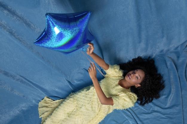 横になって青い風船で遊ぶ若い黒人女性