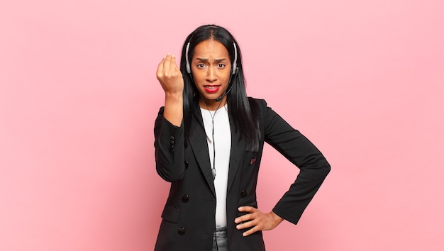 Young black woman making capice or money gesture, telling you to pay your debts!. telemarketing concept