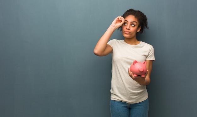 Молодая чернокожая женщина делая жест spyglass. она держит копилку.