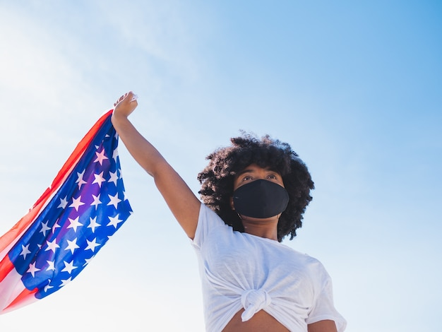 Young black woman outdoors, wearing a protective mask against coronavirus and holding a usa flag