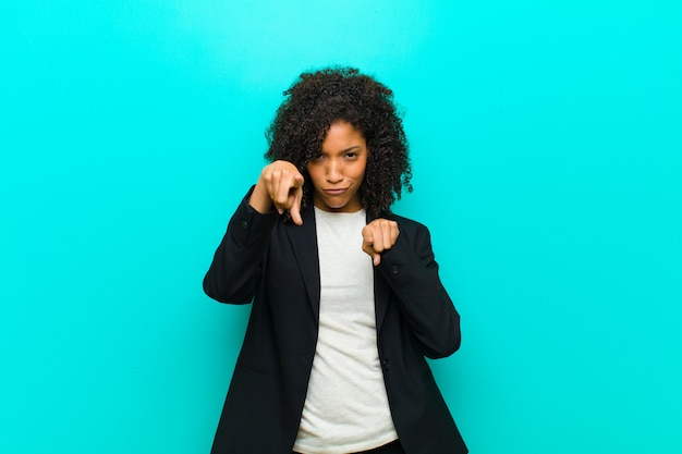 Young black woman pointing forward with both fingers and angry expression, telling you to do your duty against blue wall