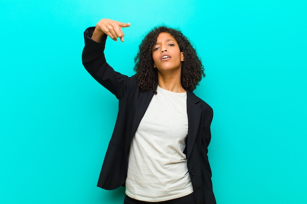 Young black woman pointing with an angry aggressive expression looking like a furious, crazy boss against blue wall