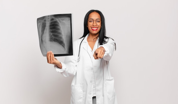 Young black woman pointing with a satisfied, confident, friendly smile, choosing you. physician concept