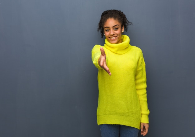 Young black woman reaching out to greet someone