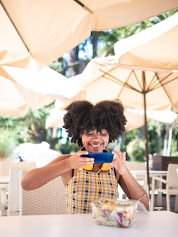 Young black woman sat on a terrace and taking a photo to a green salad, healthy food concept