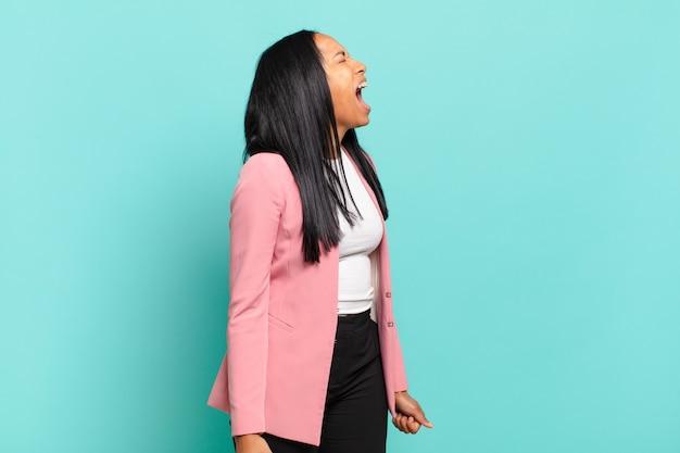 젊은 흑인 여성이 격렬하게 비명을 지르며 공격적으로 소리를 지르며 스트레스를 받고 화난 것처럼 보입니다. 비즈니스 개념