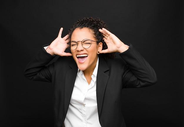 Молодая негритянка кричит в панике или гневе, шокирована, испугана или взбешена, с руками рядом с головой на черной стене
