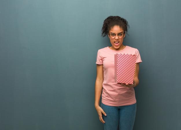 Молодая негритянка кричала очень злая и агрессивная. она держит ведро с попкорном.