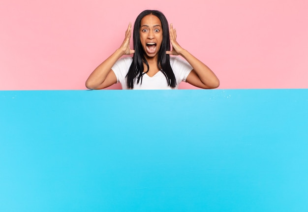 Young black woman screaming with hands up in the air, feeling furious, frustrated, stressed and upset. copy space concept