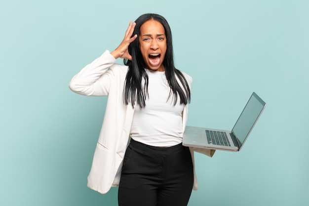 Young black woman screaming with hands up in the air, feeling furious, frustrated, stressed and upset. laptop concept