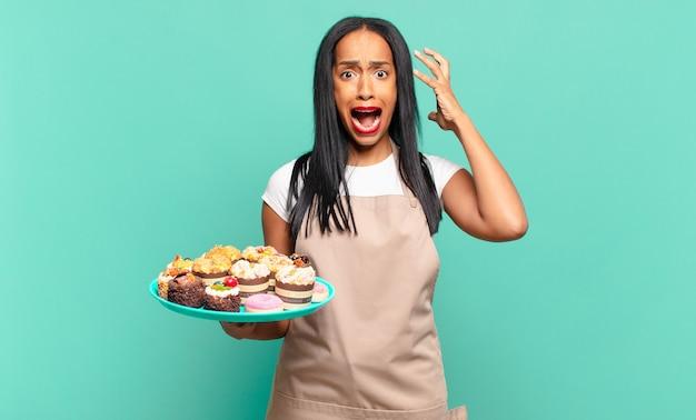 젊은 흑인 여성이 손을 높이 들고 비명을 지르며 분노하고, 좌절하고, 스트레스를 받고, 화가 났습니다. 베이커리 요리사 개념