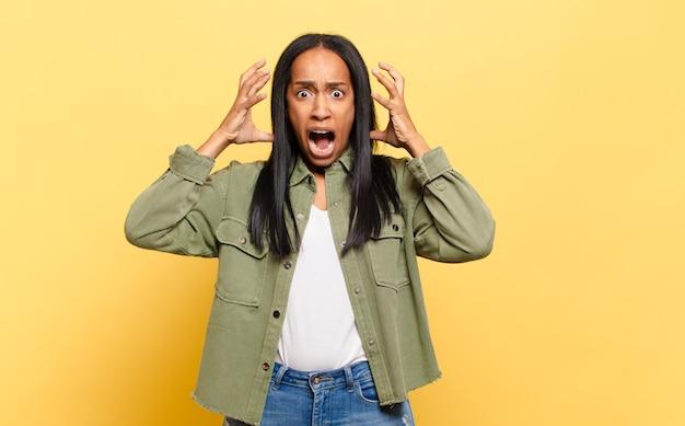 Молодая темнокожая женщина кричит с поднятыми руками, чувствуя ярость, разочарование, стресс и расстройство